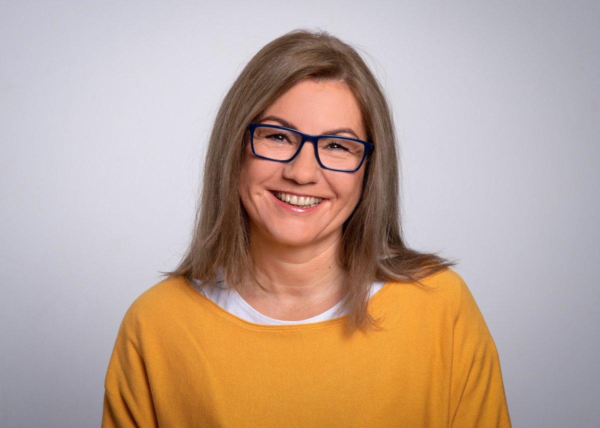 Auf dem Foto ist Aleksandra Riepe-Darsznik vor einem hellgrauen Hintergrund zu sehen. Sie hat hellbraune - graue schulterlange Harare und trägt eine dunkle eckige Brille. Sie trägt ein weißes T-Shirt und einen senfgelben Pullover und lächelt freundlich in