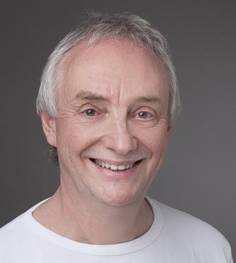 André Henzmann hat hellgraue Haare und trägt ein weißes T-Shirt. Das Portraitfoto ist vor einem grauen Hintergrund aufgenommen worden