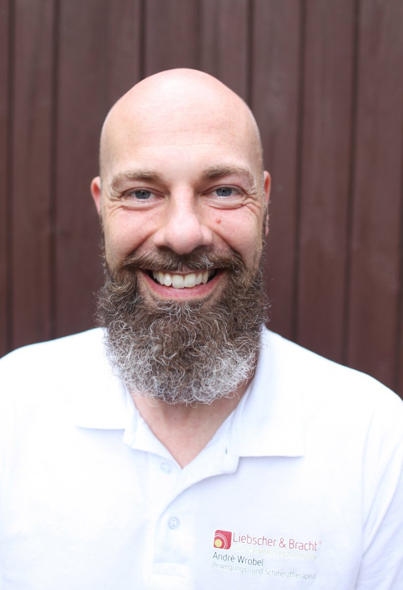 Das Foto zeigt den Bewegungs- und Schmerztherapeuten André Wrobel vor einem braunen Holzhintergrund. Er lacht in die Kamera und trägt ein weißes Liebscher & Bracht Polo T-Shirt. Er hat einen Glatze aber einen langen braun-grauen Vollbart.