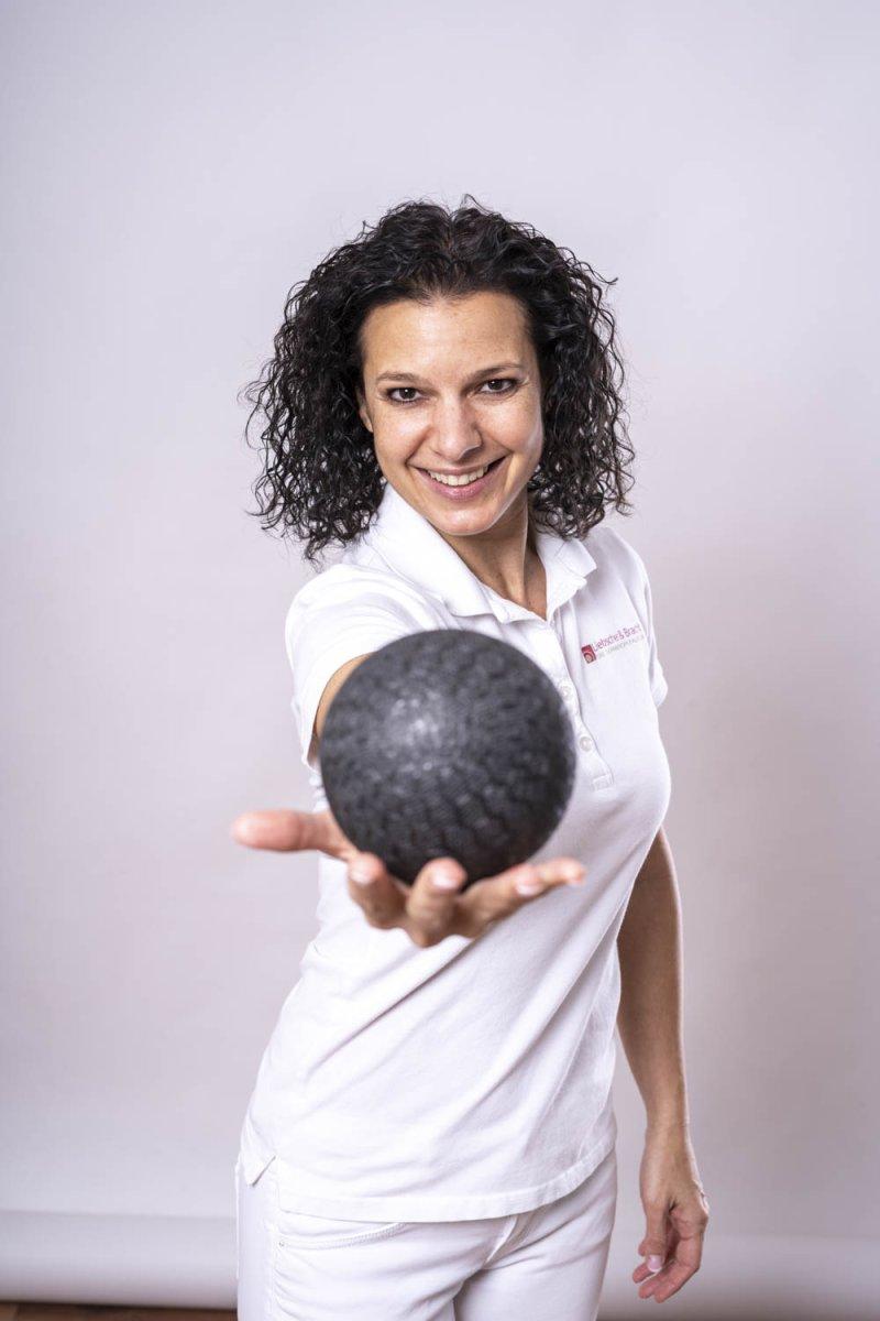 Das Foto zeigt die Schmerzspezialistin Andrea Cramer vor einem hellen Hintergrund. Sie hält eine Faszien Kugel in der Hand und streckt sie in Richtung Kamera. Die Wiesbadnerin hat schwarze mittellange Locken und trägt weiße Kleidung.