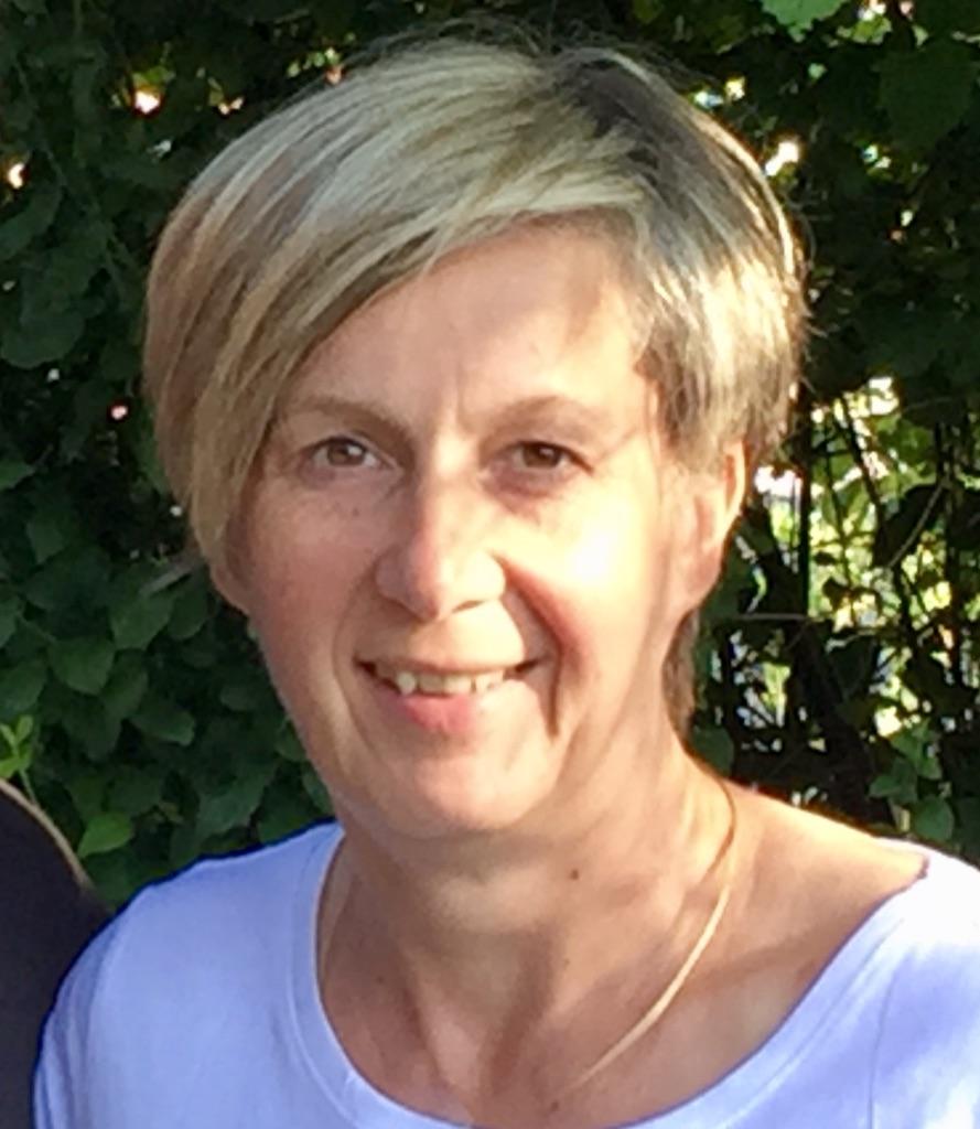 Das Foto zeigt Angela von Ziehlberg vor einem grünen Busch. Sie wird von der Seite her von der Sonne angeleuchtet. Sie hat kurze blonde Haare und trägt ein helles T-Shirt.
