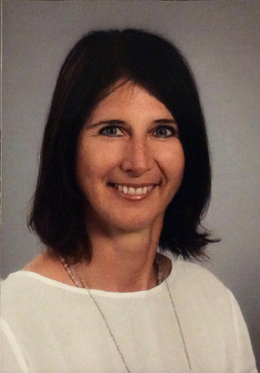 Das Foto zeigt Angelika Unterreiner aus Geisenhausen vor einem hellgrauen Hintergrund. Sie hat schulterlange schwarze Haare und lacht in die Kamera. Sie trägt ein weißes Shirt und eine lange silberne Kette.