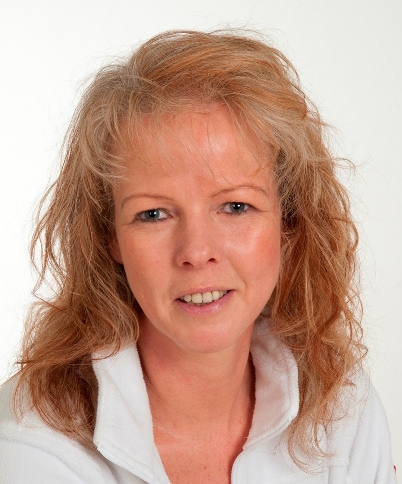 Das Portraitfoto zeigt die Heilpraktikerin Anja Ziegler aus Freystadt. Sie hat blonde lockige halblange Haare und trägt eine weiße Bluse.