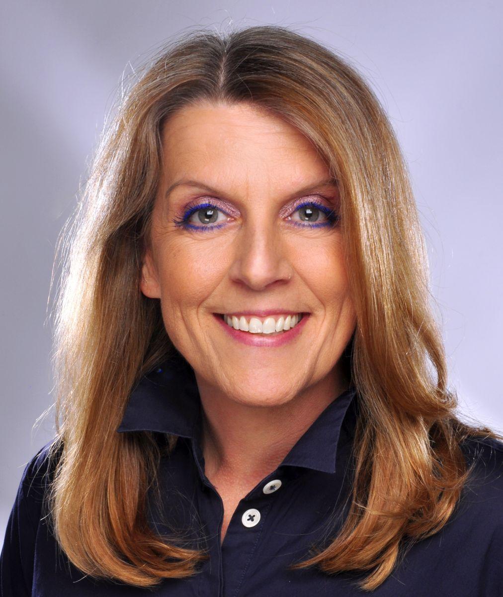 Auf dem Foto sieht man die Heilpraktikerin Annette Klink aus Wiesbaden vor einem helllila Hintergrund. Sie hat lange hellbraune Haare und trägt ein dunkelblaues Polo T-Shirt. Sie lacht in die Kamera und trägt einen lilalen Lidstrich.