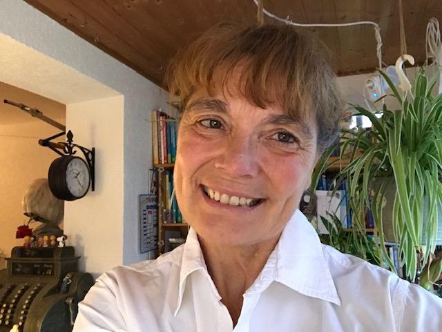 Auf dem Foto ist Astrid von Appen aus Oranienburg zur sehen. Im Hintergrund ist ein Wohnbereich mit einer großen Uhr zu erkennen. Sie hat ihre braunen Haare zusammen gebunden und hat einen geraden Pony sowie burschikose Augenbrauen. Auf dem Bild trägt sie