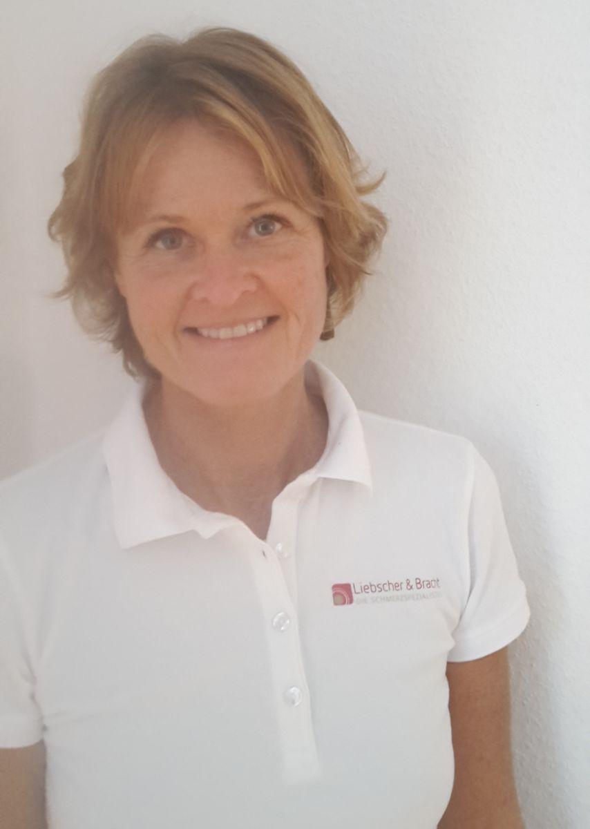 Das Foto zeigt Babett Titzmann in einem weißen Liebscher & Bracht Polo T-Shirt. Sie steht an einer weißen Wand gelehnt und hat blonde mittellange Haare.