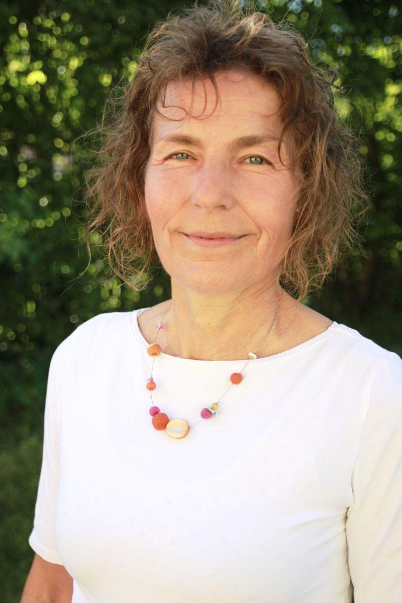 Auf dem Foto ist Bärbel Schröder aus Rockenhausen vor einem grünen Naturhintergrund zu sehen. Sie hat kinnlange braune Locken und trägt ein weißes T-Shirt mit einer roten Kette.