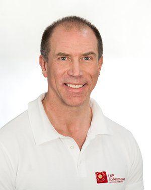 Der Heilpraktiker Bernd Huber sitzt lächelnd vor einem weißen Hintergrund. Er trägt ein weißes Liebscher & Bracht Polo T-Shirt und hat kurze schwarzgraue Haare.