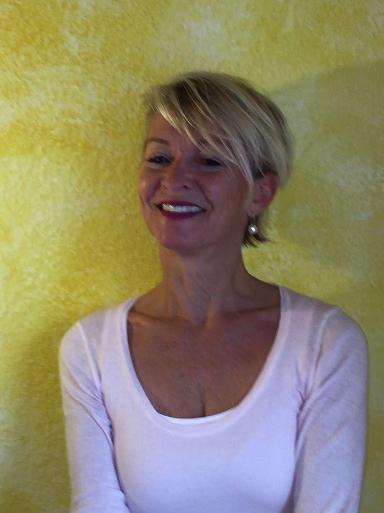 Auf dem Foto ist Bettina Luise Winter vor einer gelben Wand zu sehen. Sie hat kurze blonde Haare. Die aus Ettlingen stammende Heilpraktikerin trägt Perlenohrringe und ein weißes Shirt.