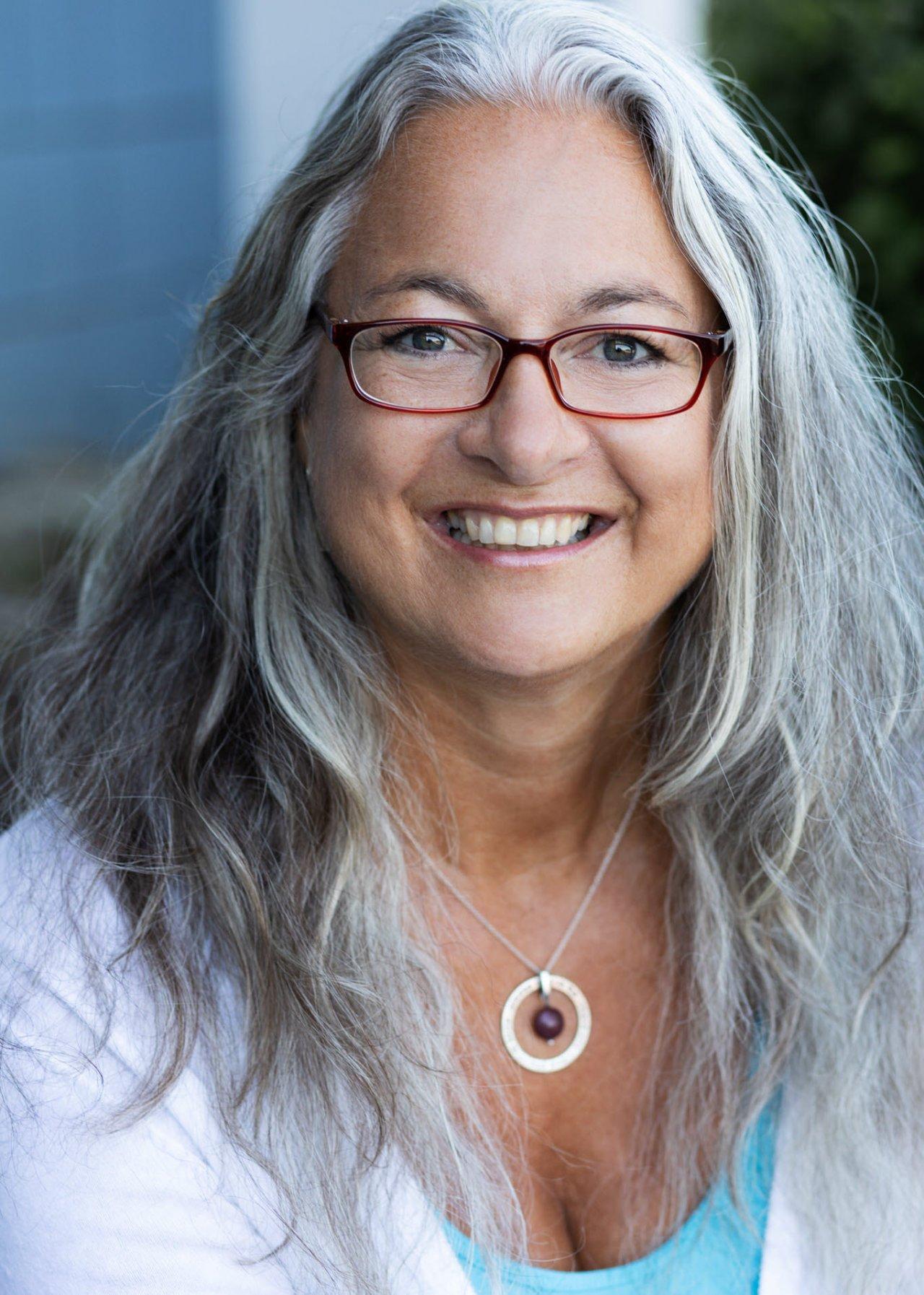 Birgit Fuchsenthaler, Qualitätspartnerin aus Neckargemünd, steht vor einem weißen Hintergrund. Sie hat lange graue Haare und trägt neben einem weißen Liebscher & Bracht T-Shirt, eine bunte runde Brille.