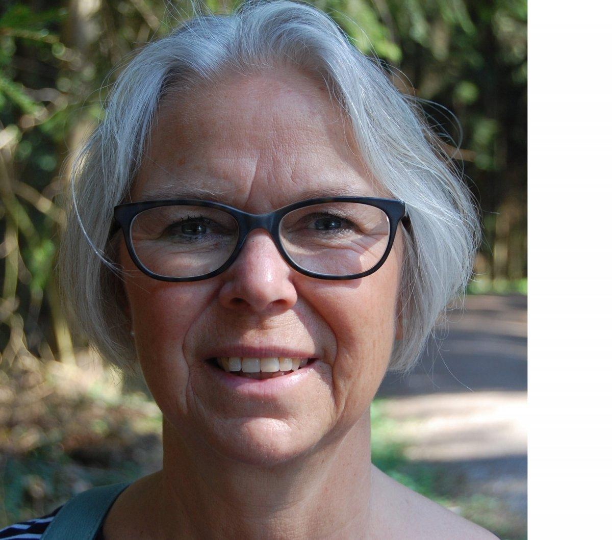 Das Foto zeigt Brigitta Ineichen vor einem Naturhintergrund. Sie hat kinnlange graue Haare und trägt eine dunkle Brille. Sie lächelt in die Kamera.