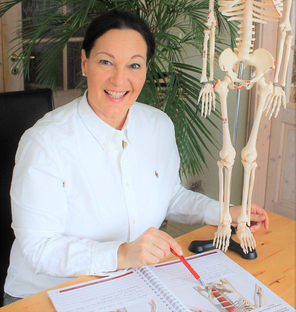 Das Foto zeigt Christina Kiefer aus Coburg sitzend an einem Schreibtisch. Sie lacht in die Kamera und zeigt mit einem Stift in einem Buch auf eine Abbildung. Neben der anderen Hand steht ein Modellskelett. Sie hat dunkelbraune Haare, die sie als Zopf träg