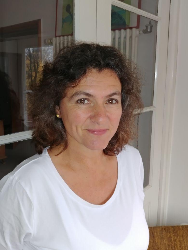 Das Foto zeigt Christine Höltke aus Bad Tölz. Sie hat schulterlange braune lockige Haare und trägt ein weißes T-Shirt.
