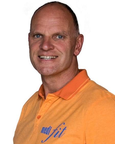 Auf dem Foto ist Christof Schreiner aus Wolfhagen zu sehen. Er hat eine Halbglatze und ganz kurzes dunkles Haar. Er trägt ein orangenes Polo T-Shirt mit dem Logo seines Gesundheitszentrums.