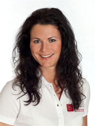 Auf dem Foto ist Cornelia Teichmann-Heyne aus Chemnitz vor einem weißen Hintergrund zu sehen. Sie hat lange braune lockige Haare und lächelt in die Kamera. Auf dem Bild trägt sie ein weißes Polo T-Shirt.