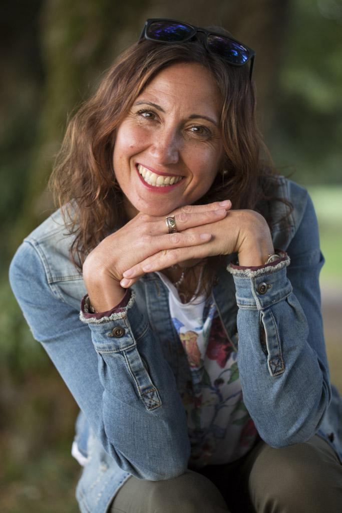 Daniela Gollmitzer sitzt lachend und stützt ihre Arme auf den Knien ab. Auf ihren Händen stützt sie wiederrum ihren Kopf ab. Sie hat lange braune Haare und trägt eine Sonnenbrille auf der Stirn. Dazu trägt sie ein weißes T-Shirt und eine Jeans Jacke.