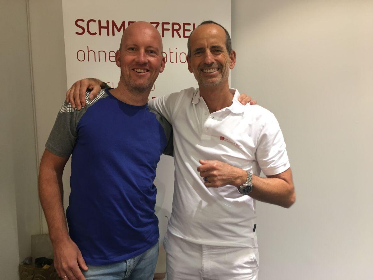 Das Foto zeigt Dennis Finke aus Minden neben Roland Liebscher-Bracht. Im Hintergrund sieht man ein Schmerzfrei Plakat. Dennis Finke hat eine Glatze und trägt ein blaues T-Shirt und lacht in die Kamera.