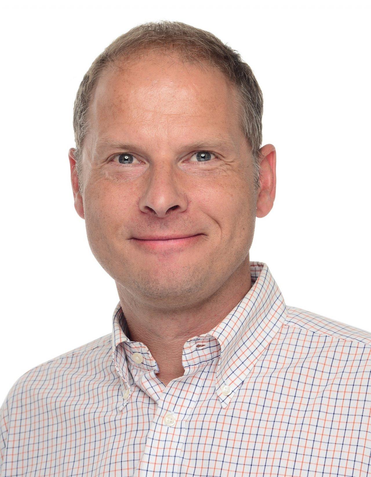 Das Foto zeigt den lächelnden Heilpraktiker Dirk Peretzki. Dieser trägt ein weißes Liebscher & Bracht Polo T-Shirt und hat kurze braune Haare.
