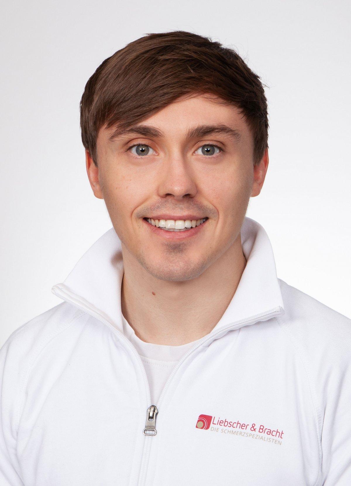 Der Sportwissenschaftler aus Hannover Dominik Machner ist im Portrait vor einem weißen Hintergrund fotografiert. Er hat braune Haare und trägt eine weiße Liebscher & Bracht Jacke.