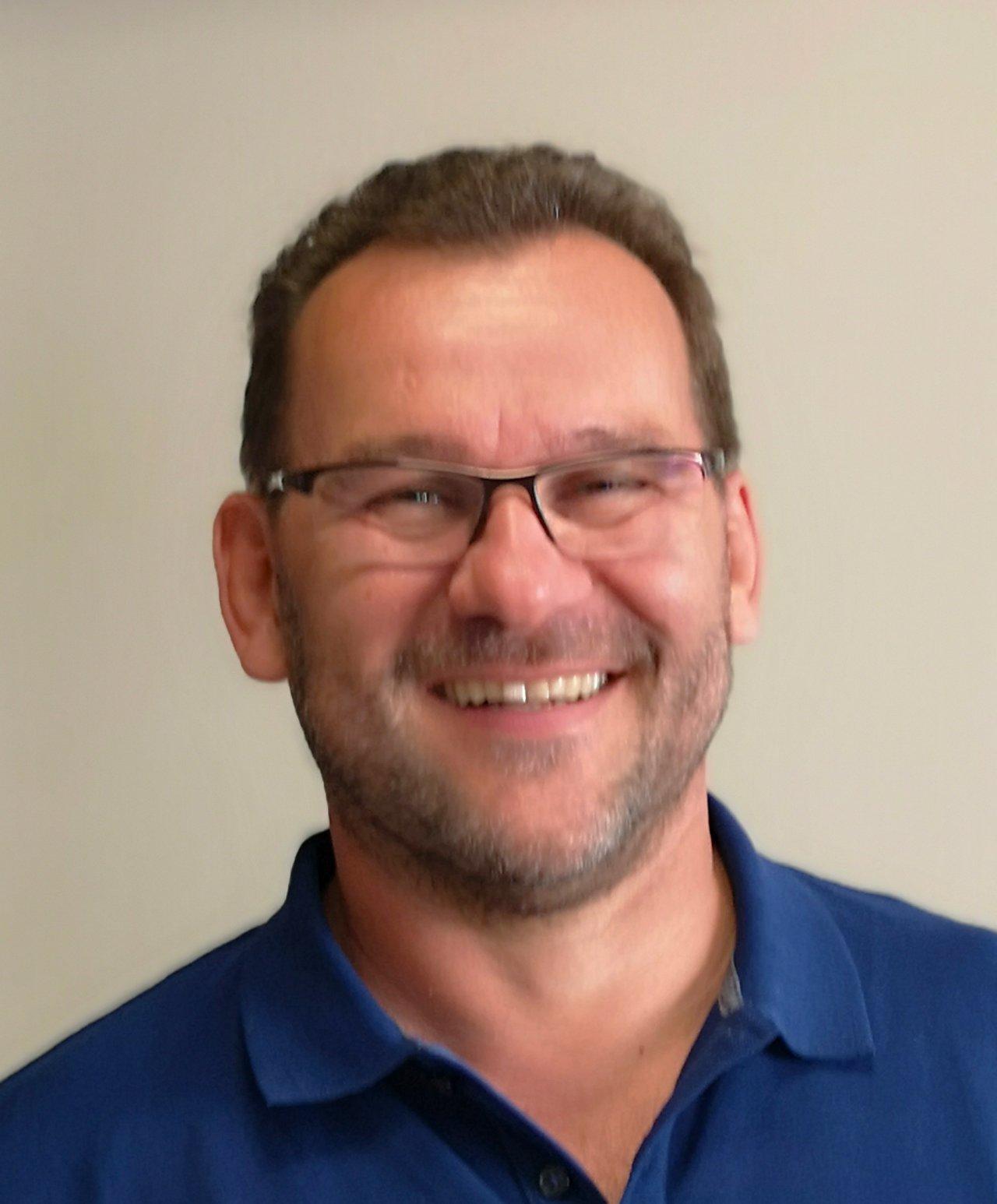 Das Foto zeigt den lachenden Dr. Arnd Schürmann aus Vilshofen an der Donau. Er wurde vor einem weißen Hintergrund fotografiert und trägt ein blaues Polo T-Shirt sowie eine eckige Brille. Außerdem hat er braunes kurzes Haar.