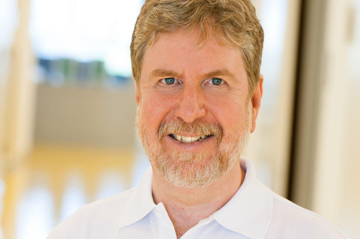 Das Portraitfoto zeigt Dr. med. Harald Kirchmair aus Innsbruck. Er steht vor einem hellen Hintergrund und lächelt in die Kamera. Er hat blond-graues Haar, sowie einen Vollbart.
