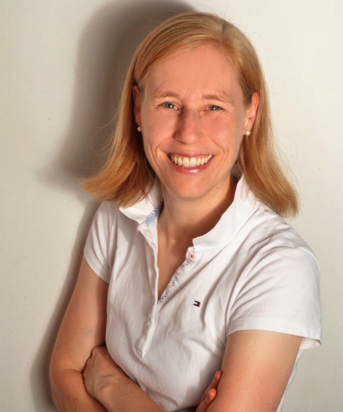 Das Foto zeigt Dr. med. K-Lisa Junika aus Bremen. Sie lehnt an einer weißen Wand und lacht in die Kamera. Sie hat rot blonde schulterlange Haare und trägt ein weißes Polo T-Shirt.