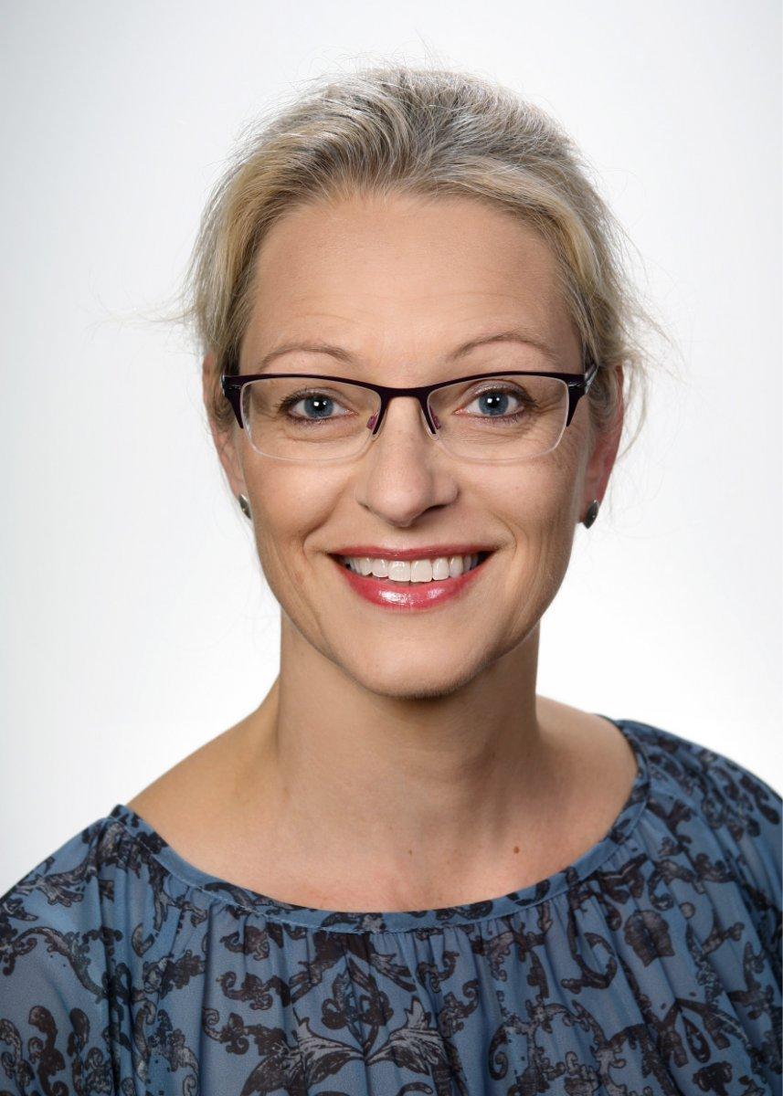 Im Portraitfoto ist Dr. med. Miriam Scheidthauer frontal mit blonden Haaren, Brille und gefleckter, blauer Bluse zu sehen.