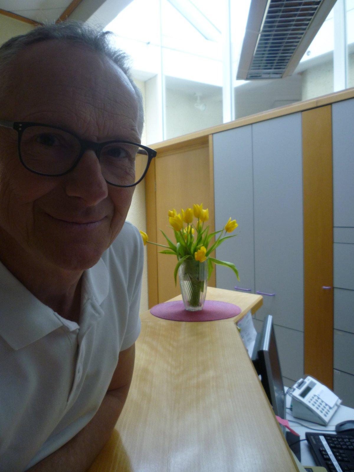 Auf dem Foto lehnt Dr. Thomas Werner aus Bad Königshofen lehnt an einer Theke. Im Hintergrund ist ein Blumenstrauß und ein Schrank zu sehen. Dr. Werner hat kurze Haare und trägt eine schwarze eckige Brille und ein weißes Polo T-Shirt.