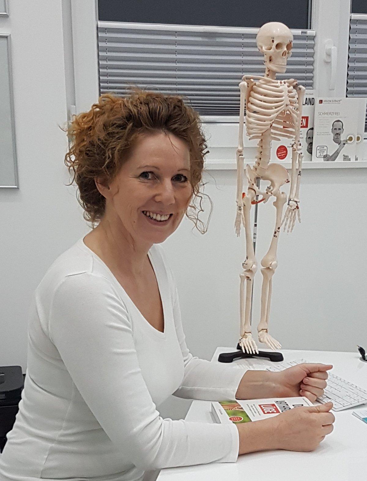 Das Foto zeigt die Heilpraktikerin Daniela Eisenhardt sitzend an einem Tisch. Im Hintergrund steht ein Modell Skelett und zwischen ihren Händen auf dem Tisch liegt ein Buch von Liebscher & Bracht. Sie hat braune Locken, die sie zusammen gebunden hat und t
