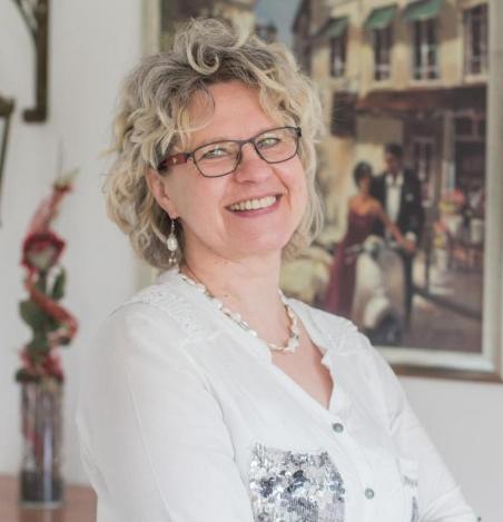 Ellen Döscher aus Bad Zwischenahn steht vor einem Gemälde. Sie lacht in die Kamera und trägt eine dunkle eckige Brille. Sie hat kinnlange blonde lockige Haare und auf dem Foto trägt sie eine weiße Bluse und silbernen Schmuck.