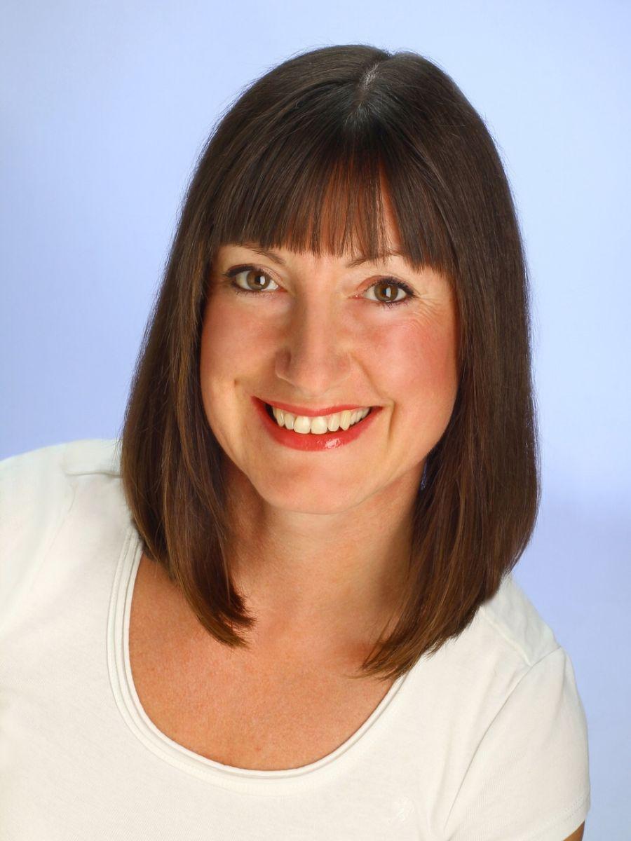 Vor dem hellblauen Hintergrund sieht man als Portrait die Schmerztherapeutin Ramona Franke sympathisch lächeln. Sie hat braune mittellange Haare mit Pony. Sie trägt ein weißes T-Shirt.