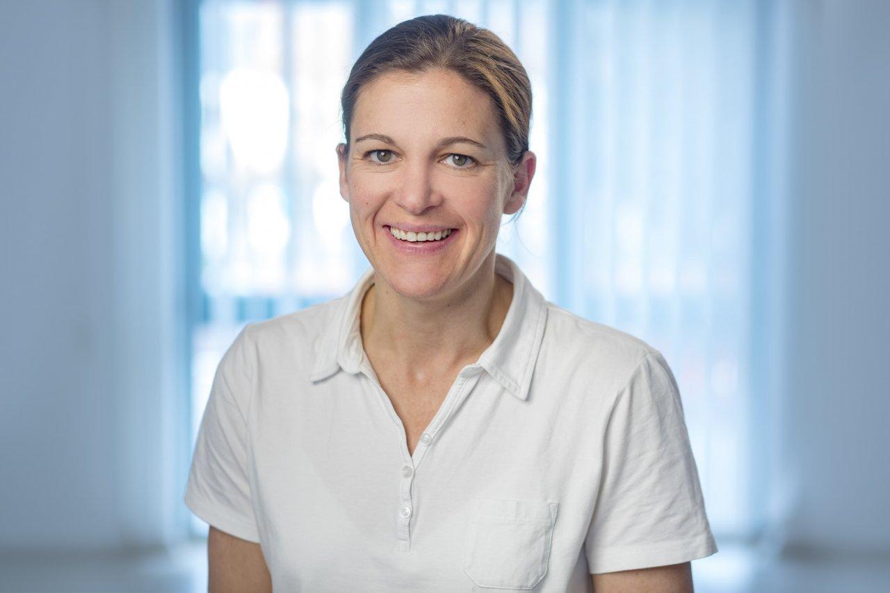 Das Foto zeigt die Physiotherapeutin Friederike Zilch-Bratzler. Im Hintergrund ist ein großes Fenster zu erkennen. Sie trägt Ihre Haare zu einem Zopf und ein weißes Polo T-Shirt.
