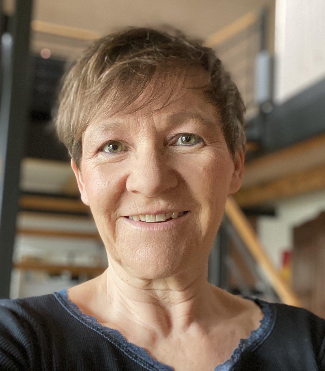 Das Portraitfoto in schwarz weiß, zeigt Gabriele Furhan mit kurzen Haaren und einer Brille. Sie trägt ein helles Polo T-Shirt. Der Hintergrund ist ebenfalls hell.