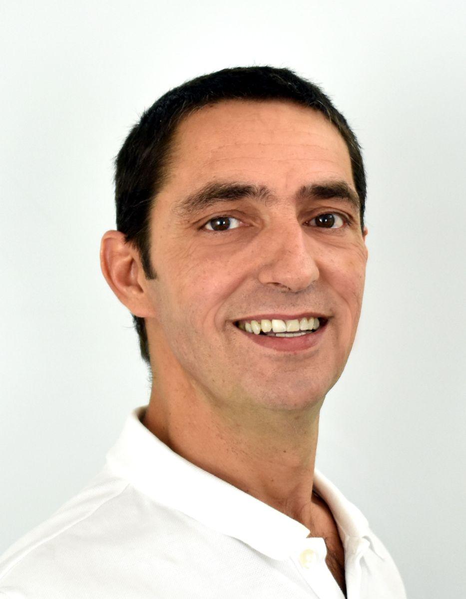 Das Portraitfoto zeigt Guido Bucher aus der EIM Praxis in Lachen schräg von der Seite. Er hat schwarze kurze Haare und trägt ein weißes Polo T-Shirt.