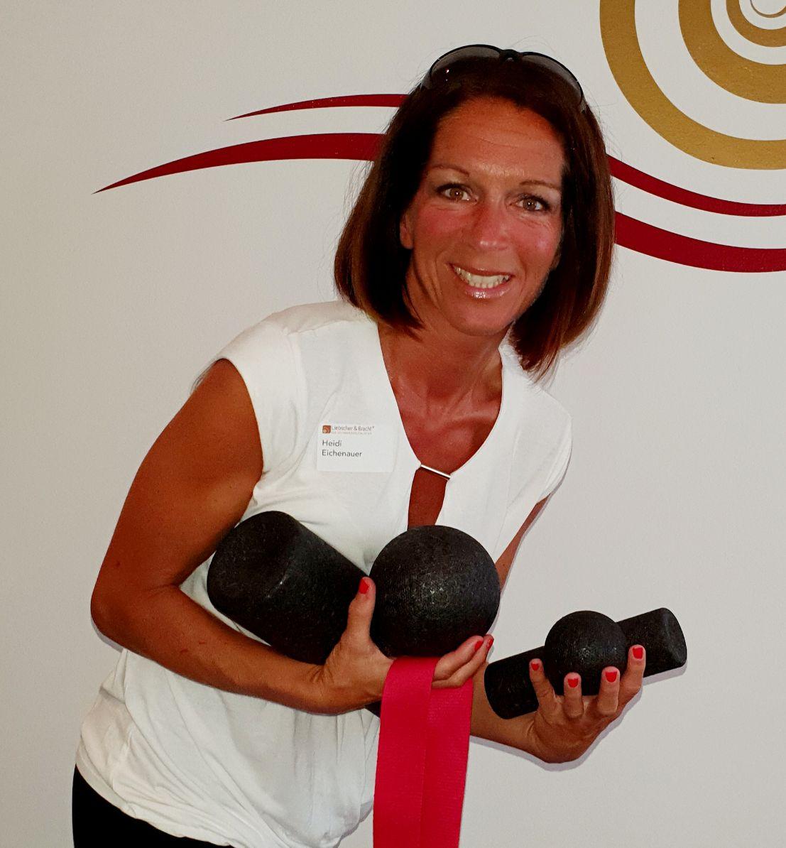 Auf dem Foto ist Heidi Eichenauer aus Lampertheim zu vor einer weißen Wand zu sehen. Sie steht mit dem Oberkörper schräg nach vorne und hält in ihren Händen die Faszienrollen und die Übungsschlaufe. Sie hat kinnlange braune Haare und trägt eine weiße Blus