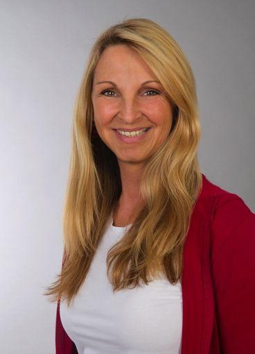 Sabine Hoeher aus Berlin steht vor einem hellgrauen Hintergrund. Sie trägt weiße Kleidung und eine rote Strickjacke. Die Heilpraktikerin und Qualitätspartnerin lächelt freundlich und hat lange blonde Haare.