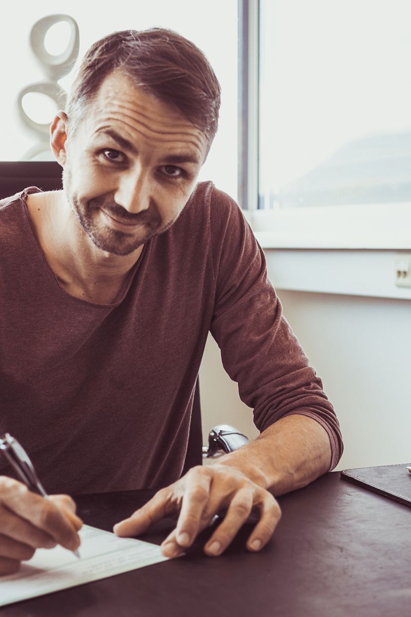 Auf dem Foto ist Herbert Scheipl aus Elixhausen zu sehen. Er sitzt am Schreibtisch und unterschreibt gerade ein Dokument, dabei schaut er lächelnd in die Kamera. Er hat kurze braune Haare und einen Dreitagebart und trägt ein braunes Shirt.