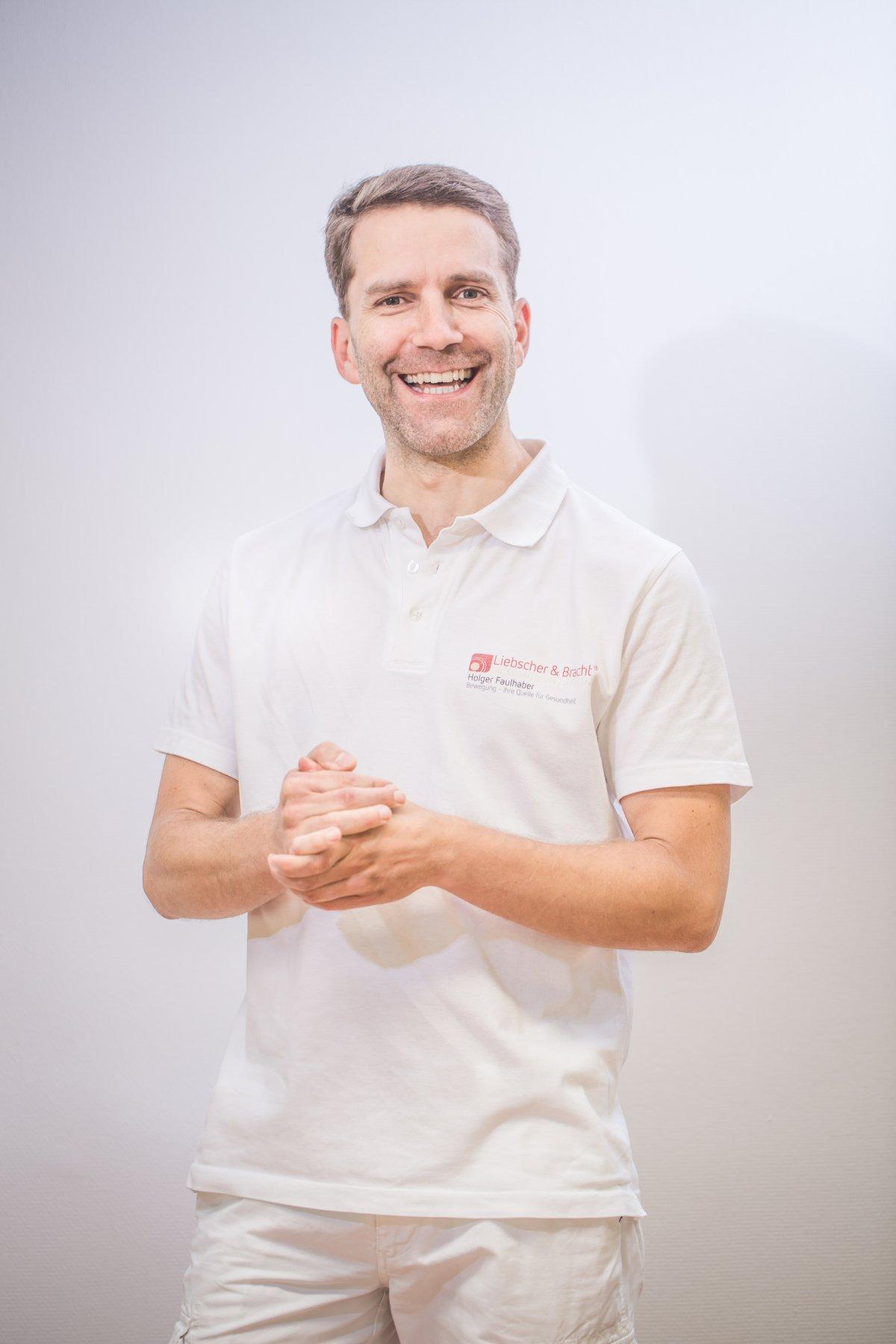 Schmerzspezialist Holger Faulhaber aus 78628 Rottweil steht sympathisch vor einer weißen Wand. Er trägt weiße Kleidung und das Liebscher & Bracht Polo T-Shirt. Er hat hellere braune Haare.
