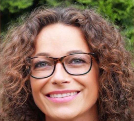 Das Foto zeigt Ines Viehrig aus Wuppertal. Sie hat braune Locken und eine braune eckige Brille. Sie lächert direkt in die Kamera.