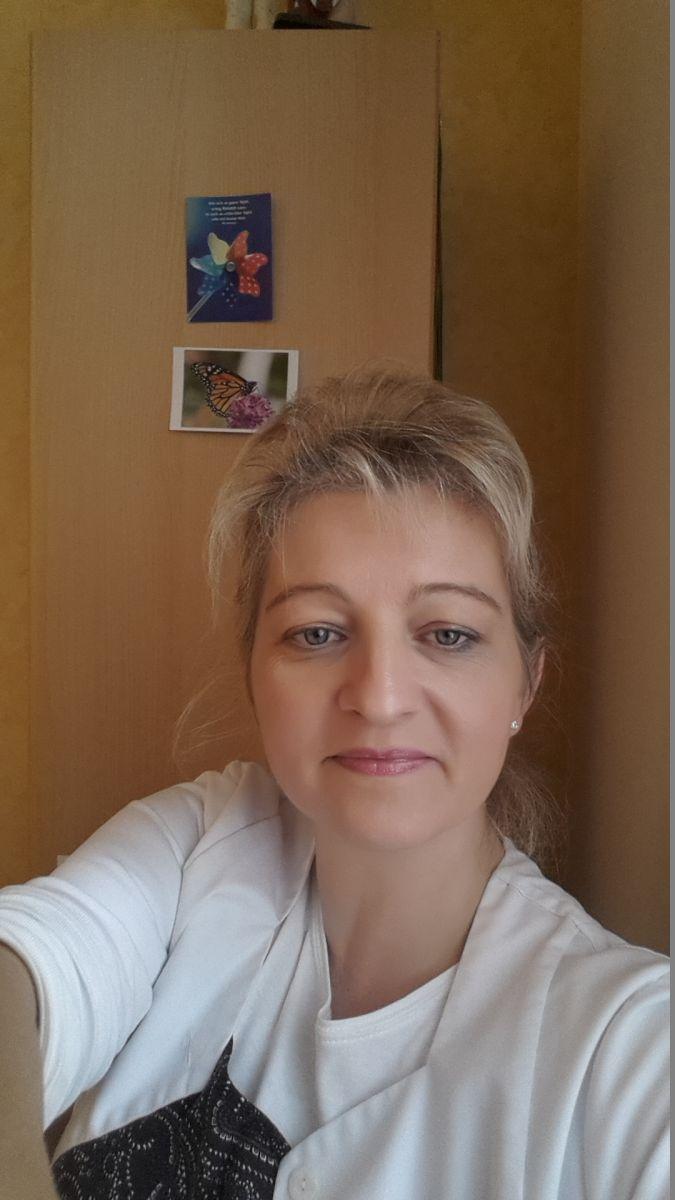 Auf dem Foto sieht man Inge Ahrens-Witte aus 27798 Hude-Wüsting vor einem holzfarbenen Hintergrund. Sie trägt ihre blonden Haare als Zopf und hat einen leichten Pony. Außerdem trägt sie weiße Kleidung mit einem schwarzen Muster drauf.
