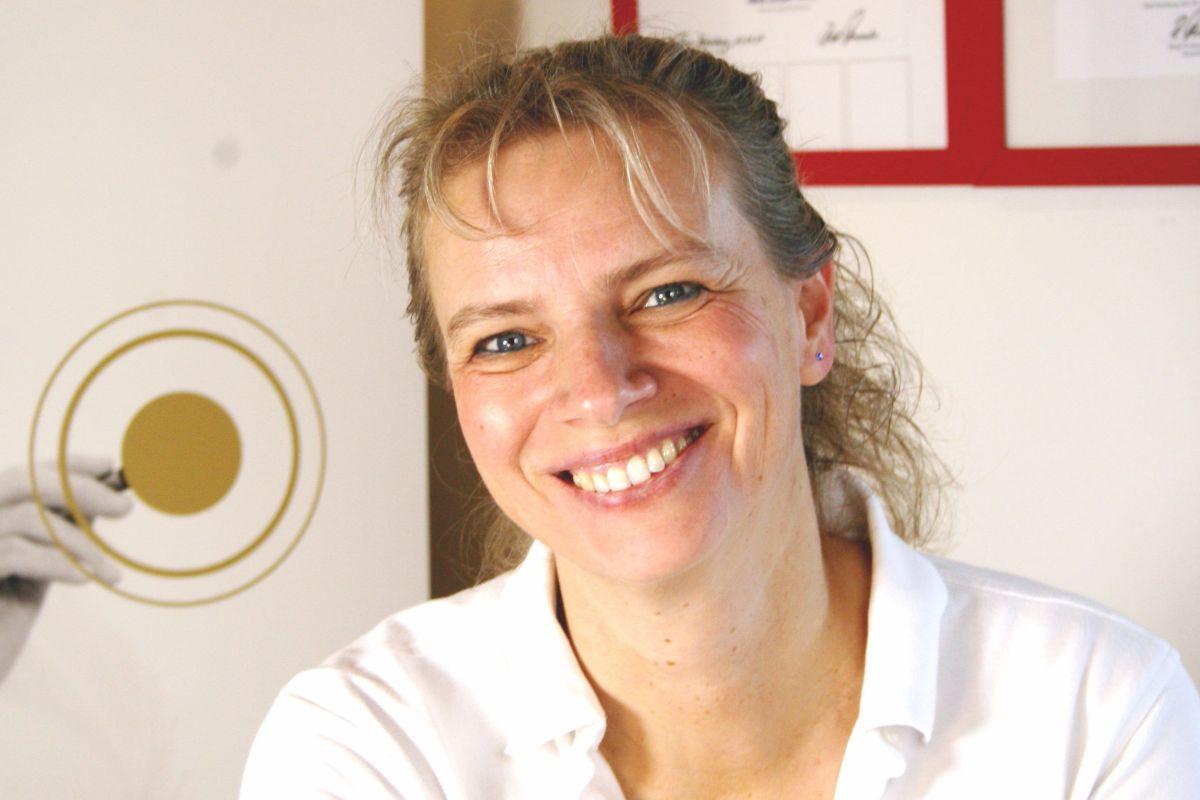 Iris Harling sitzt breit lächelnd vor einem Hintergrund mit Plakaten. Die Heilpraktikerin aus Braunschweig hat blonde lockige Haare, welche als Zopf gebunden sind.
