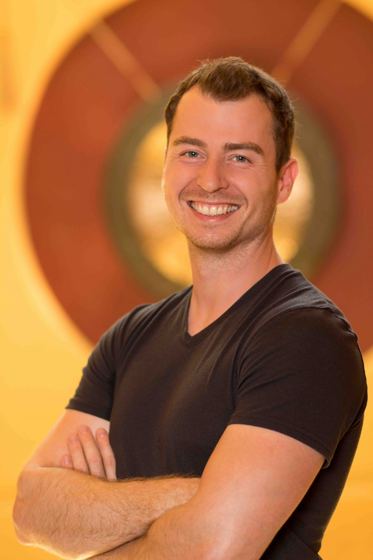Das Foto zeigt den Physiotherapeuten Jakob Parrisius aus Witzenhausen vor einem orange braunen Hintergrund. Er steht schräg und lacht in die Kamera und hat die Hände vor der Brust verschränkt. Er hat kurze braune Haare und trägt ein schwarzes T-Shirt.