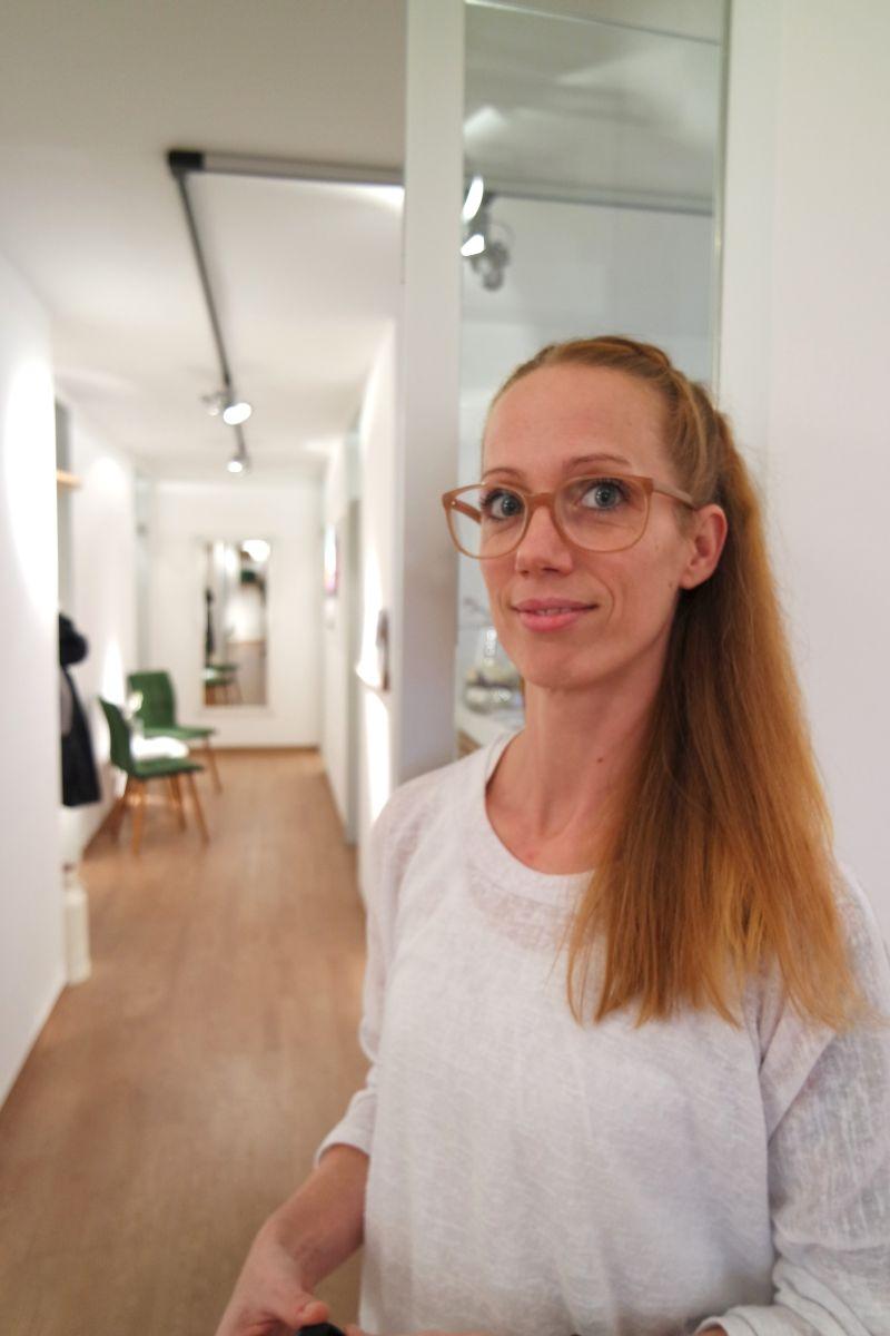Das Foto zeigt die L&B Dozentin und Schmerzspezialistin Jana Keukenbrink in einem hellen Flur. Sie hat ihr hellbraunen Haare als Zopf gebunden und trägt eine eckige braune Brille sowie ein weißes Oberteil.