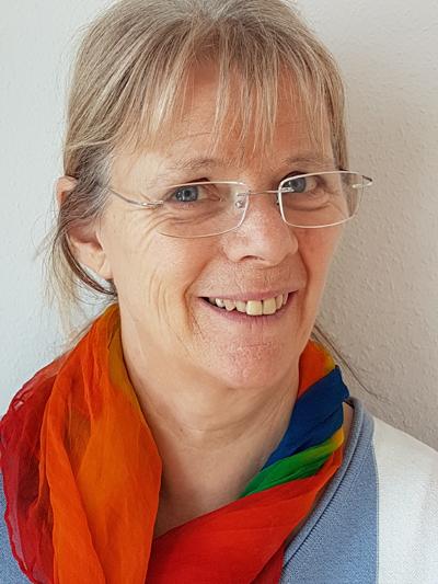 Das Foto zeigt Dr. med. Tania Urso aus Bern vor einem hellen Hintergrund. Sie hat kinnlange blonde Haare und trägt eine eckige schwarze Brille sowie einen blauen Blazer und eine rosafarbene Bluse.