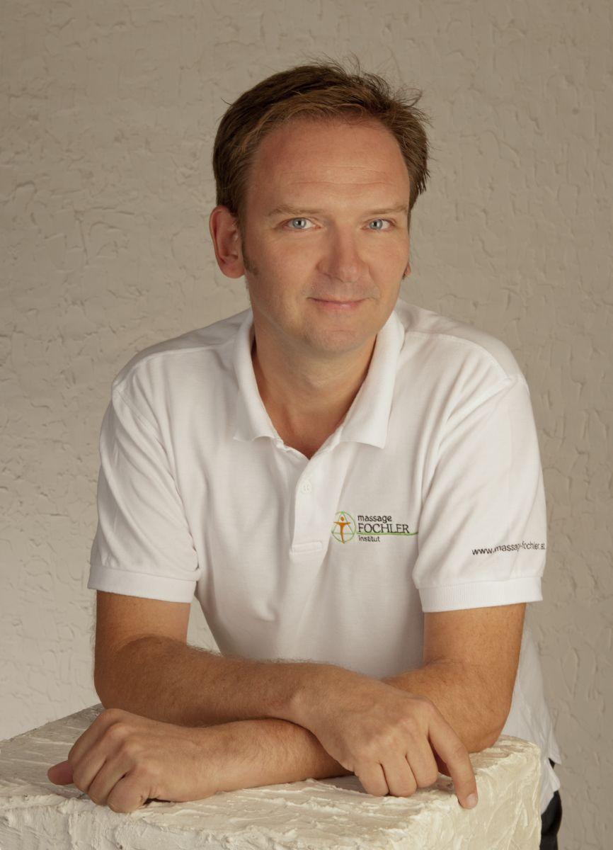 Das Foto zeigt Johannes Folcher vor einem beigen Hintergrund. Seine Arme hat er auf einem weißen Tisch abgelegt, hinter dem er steht. Er hat kurze braune Haare und trägt ein weißes Polo T-Shirt mit dem Firmenlogo.