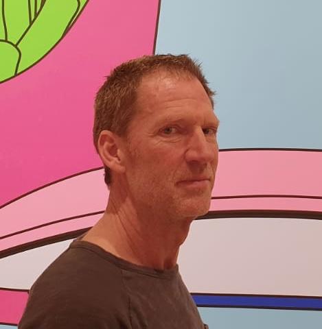 Das Foto zeigt Jors Bruseker aus Aachen vor einem bunten Hintergrund. Er hat kurzes braunes Haar und schaut seitlich in die Kamera. Auf dem Foto trägt er ein braunes T-Shirt.