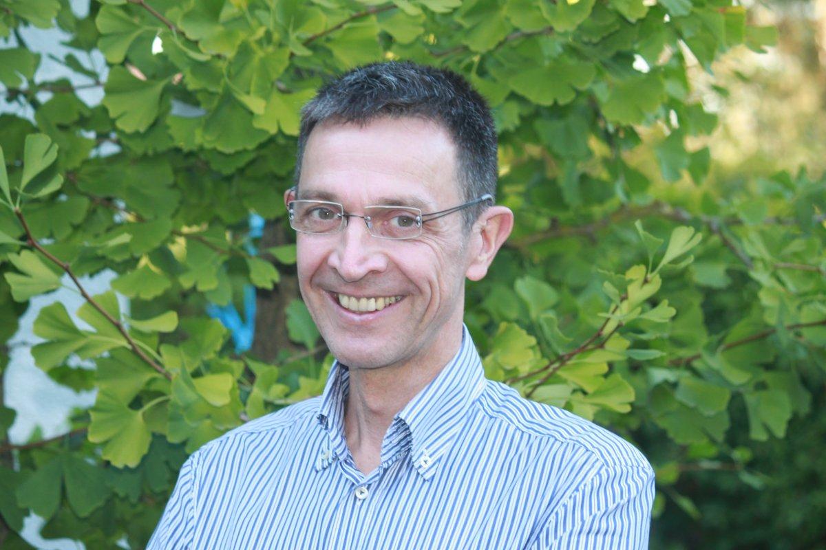 Das Foto zeigt Jürgen Mund vor einem grünen Ahornbaum. Er hat kurzes schwarz graues Haar und trägt eine randlose Brille. Er lacht in die Kamera und trägt ein blau weiß gestreiftes Hemd.