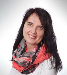 Das Foto zeigt Karin Goldbach aus Leutkirch. Sie hat lange schwarze Haare und einen geraden Pony. Sie trägt ein rot graues Tuch und ein weißes T-Shirt.