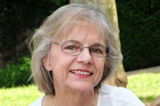 Das Foto zeigt Karin Harth aus Freigericht vor einem grünen Hintergrund. Sie hat kinnlange graue Haare und trägt eine eckige graue Brille. Auf dem Foto trägt sie ein weißes T-Shirt.