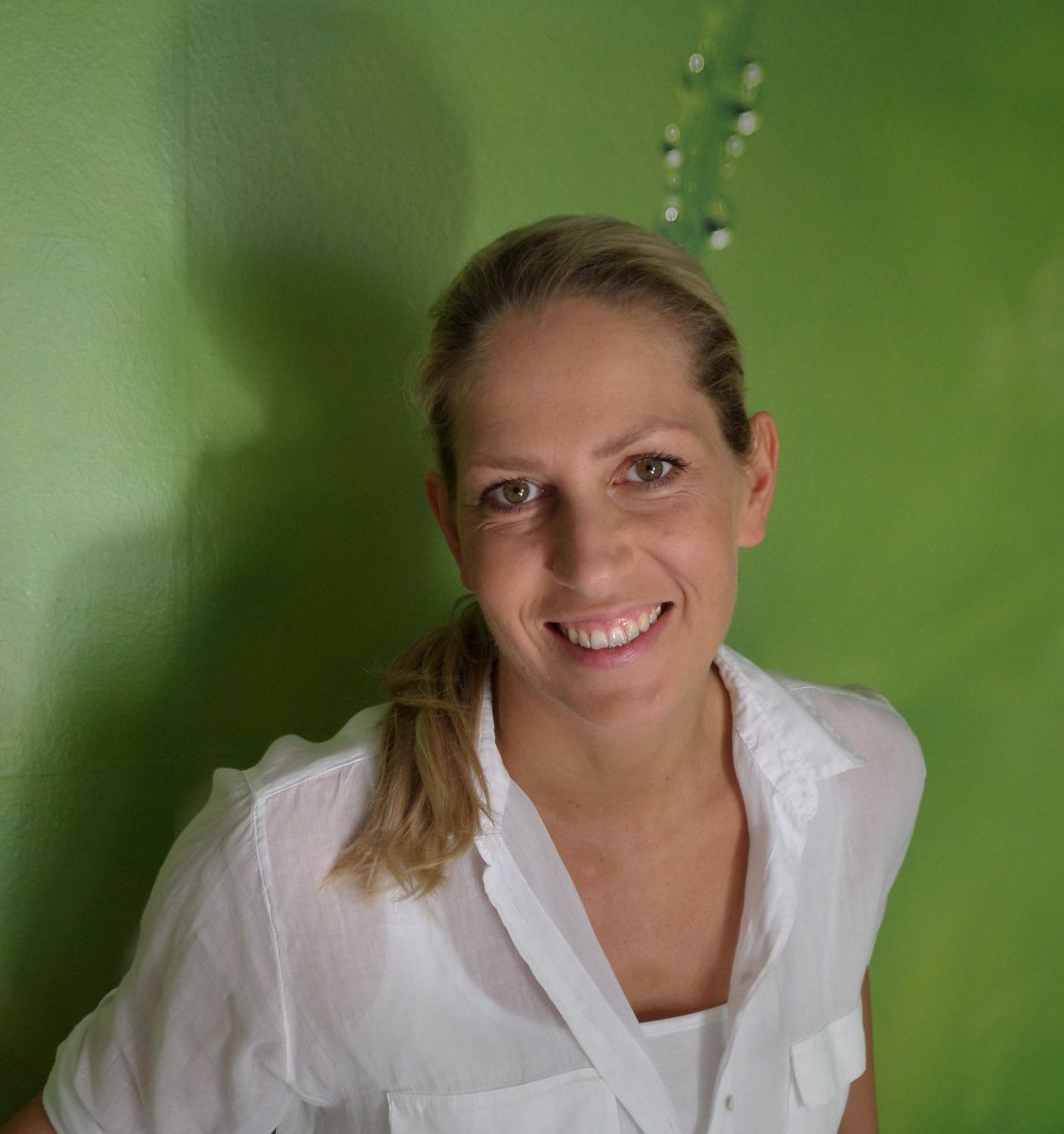 Auf dem Foto lehnt die Schmerz- und Bewegungstherapeutin aus 7053 Hornstein an einer grünen Wand. Katja Mössner lacht in die Kamera und trägt ihre langen blonden Haare zum Zopf, der auf der Schulter abgelegt ist. Sie trägt eine weiße Bluse.